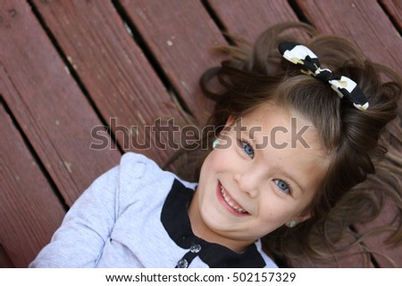 cute blue eyed girl laying on a boardwalk