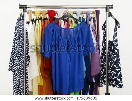 Cute blue outfits displayed on a rack. Wardrobe with colorful summer clothes and accessories.