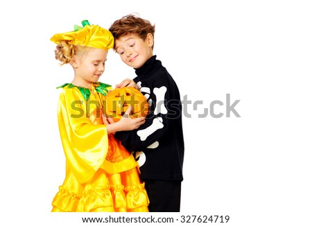 Cute boy and a girl wearing halloween costumes posing with pumpkin. Halloween. Isolated over white. - stock photo