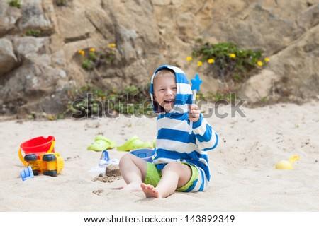 Cute boy and beach toys - stock photo