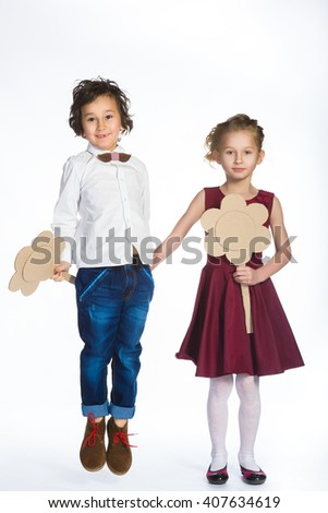 Cute boy and girl or teenagers in full length casual style blue jeans posing