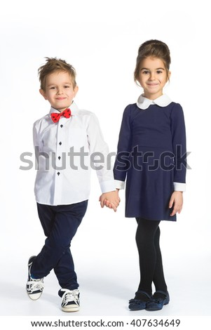 Cute boy and girl or teenagers in full length casual style blue jeans posing - stock photo