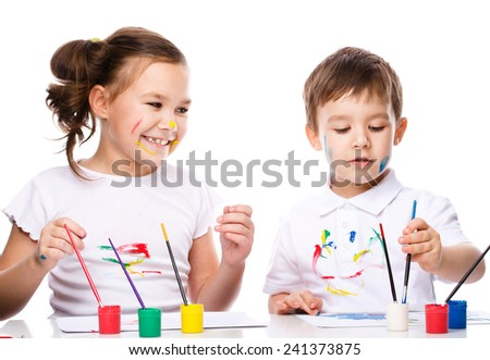 Cute boy and girl showing her hands painted in bright colors, isolated over white - stock photo
