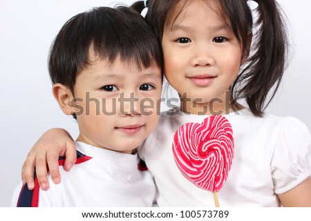 Cute boy and girl with lollipop - stock photo