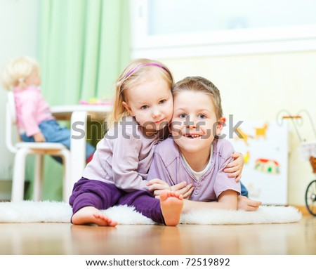 Cute boy and his little sister at home - stock photo