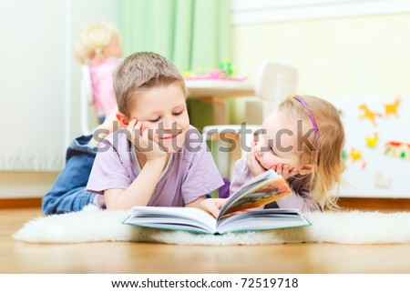 Cute boy and his little sister at home reading