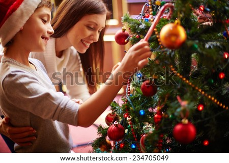 Cute boy and his mother by Christmas tree - stock photo