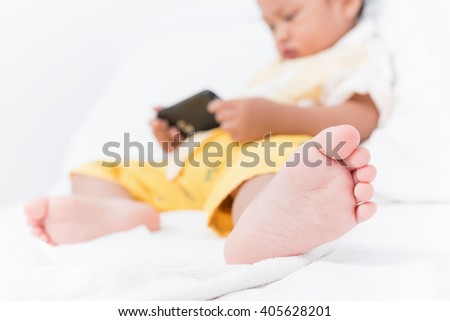 Cute boy asian baby playing a smartphone in the room. Focus on the child's feet