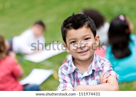 Cute boy at school looking very happy outdoors  - stock photo