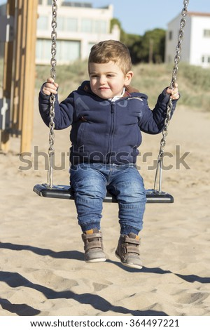 Cute boy at the beach on a swing - stock photo