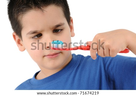 Cute boy brushing teeth isolated on white background. - stock photo