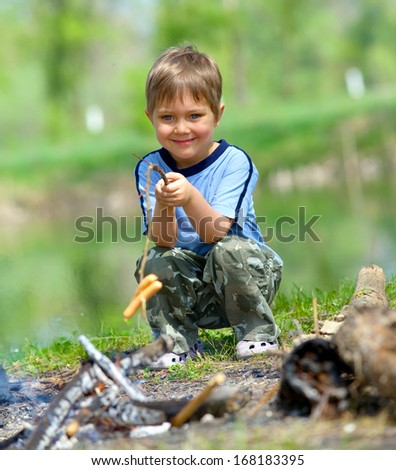 Cute boy cooking sausage by bonfire in hike. - stock photo