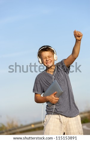 Cute boy dancing to the rhythm with headphones and digital tablet outdoors. - stock photo