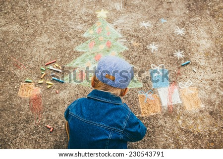 Cute boy drawing Christmas tree and gifts on the street. - stock photo