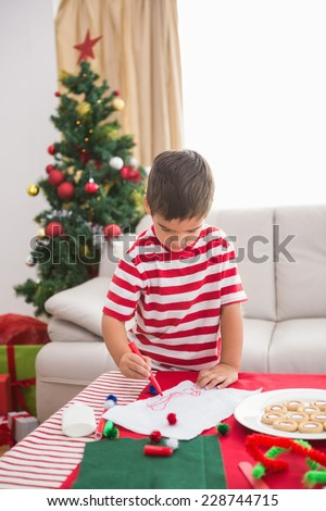 Cute boy drawing festive pictures at home in the living room - stock photo
