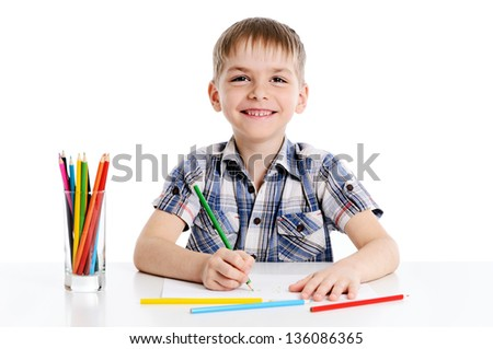 cute boy drawing with colorful pencils on white background - stock photo