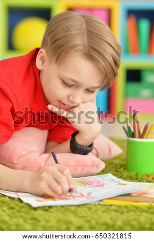 Cute boy drawing with pencils
