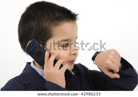 Cute boy dressed as businessman on the phone looking his watch - stock photo