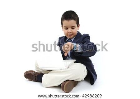 Cute boy dressed as businessman with  laptop looking his watch