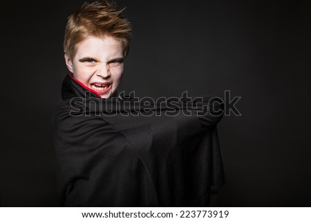 Cute boy dressed up as vampire for the halloween party. Studio portrait over black background  - stock photo