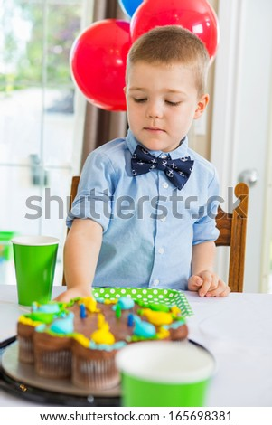 Cute boy eating birthday cake at home