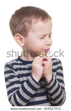 Cute boy eating sour candy on isolated white