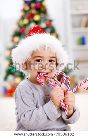Cute boy eating twisted Christmas candy in front of decorated tree - stock photo