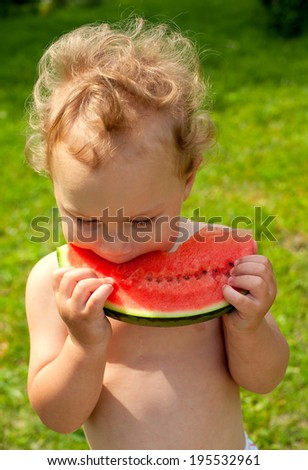 cute boy eating water melon outdoors