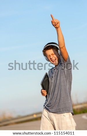 Cute boy feeling free with headphones and digital tablet outdoors. - stock photo