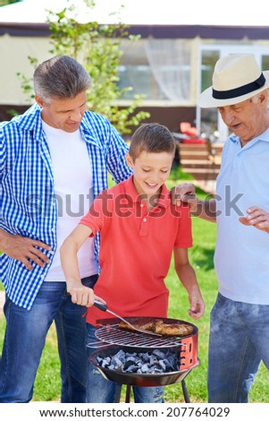 Cute boy frying sausages with his grandfather and father near by - stock photo