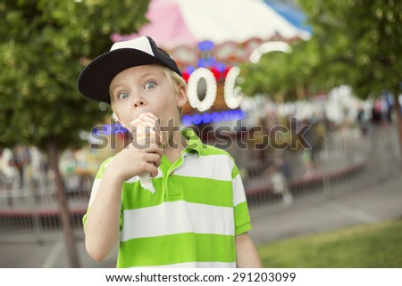 Cute boy fully enjoying an ice cream cone during a summer carnival or fair. He is making an excited expression - stock photo