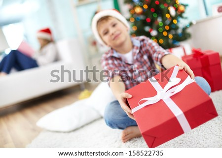 Cute boy giving big red giftbox to someone on Christmas evening - stock photo