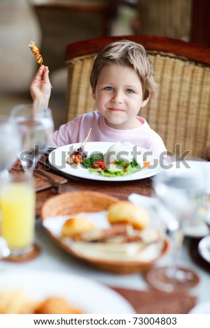 Cute boy having delicious lunch in restaurant - stock photo