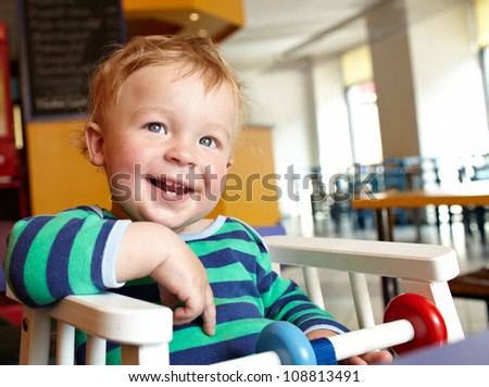 Cute boy having delicious lunch in restaurant and laughing. Natural bright colors. - stock photo
