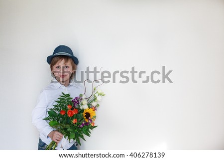 cute boy holding a beautiful bouquet of flowers  - stock photo