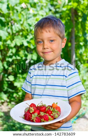 Cute boy holding plate with organic natural healthy food produce - strawberries. Vertical view - stock photo
