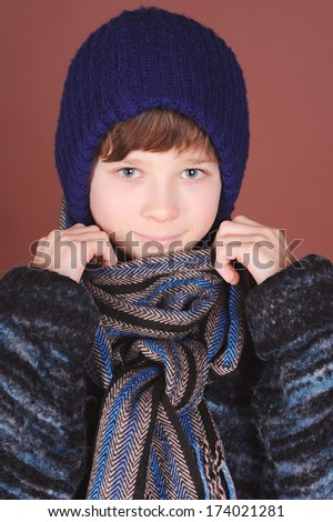 Cute boy holding scarf, wearing winter clothes