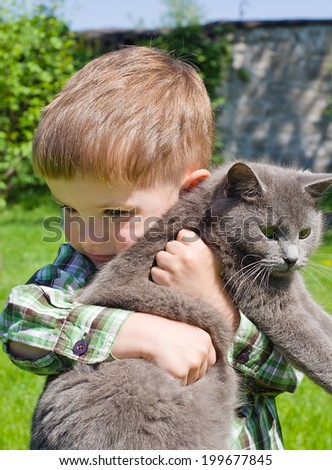 Cute boy hugs cat - stock photo