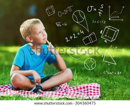 Cute boy in a park thinking - stock photo