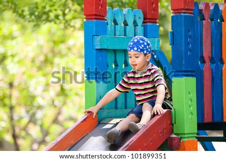 Cute boy in bandana playing on slide - stock photo