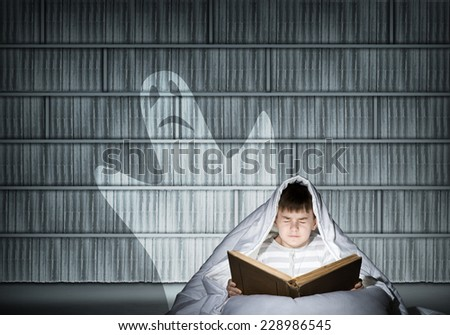 Cute boy in bed reading book under blanket - stock photo