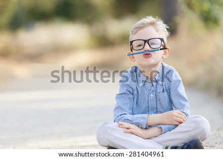 cute boy in glasses being silly, back to school concept - stock photo