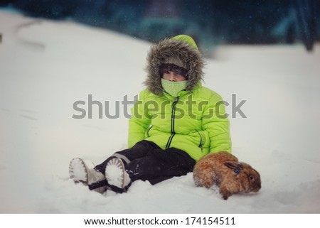 cute boy in green jacket sitting in the snow with a rabbit - stock photo