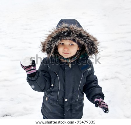 Cute boy in snowsuit holding snowball
