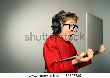 Cute boy in spectacles and headphones looking at his laptop monitor and shouting. Studio shot. - stock photo
