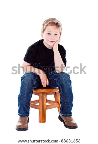 Cute boy in studio sitting on a stool - stock photo