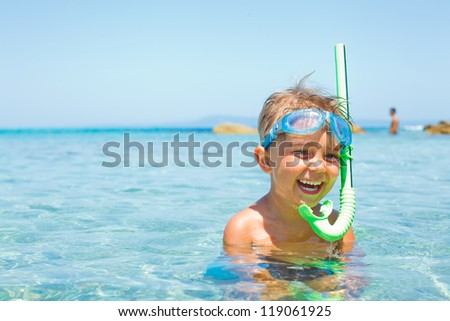Cute boy in swimming goggles and snorkel swimming in the transparent sea - stock photo
