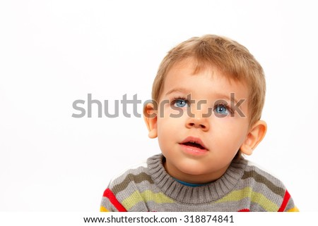 Cute boy in winter clothes looking up amazed - stock photo