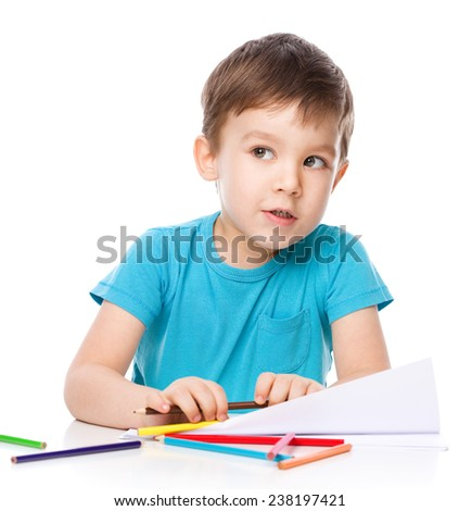 Cute boy is drawing using color pencils, isolated over white
