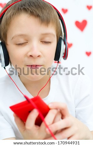 cute boy is listening to the music